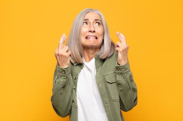 Kobieta w średnim wieku z niepokojem krzyżuje palce i liczy na szczęście ze zmartwionym spojrzeniem