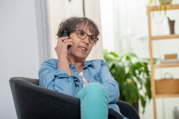 Kobieta w średnim wieku z okularami szczęśliwy rozmawiać za pomocą telefonu
