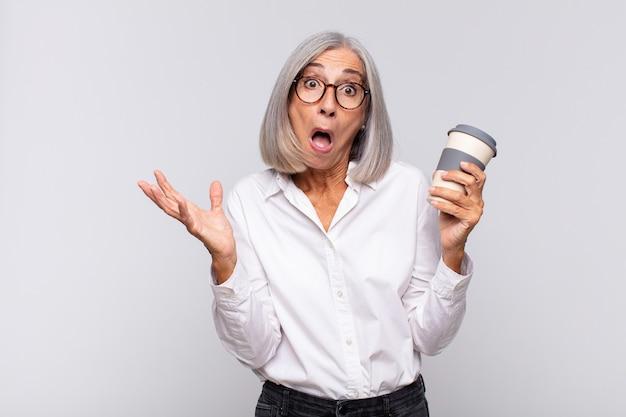Kobieta w średnim wieku z otwartymi ustami i zdumiona, zszokowana i zdumiona niewiarygodną koncepcją kawy niespodzianki