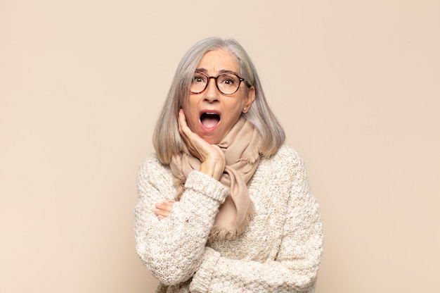 Kobieta w średnim wieku z otwartymi ustami w szoku i niedowierzaniu, z dłonią na policzku i skrzyżowanymi rękami, oszołomiona i zdumiona