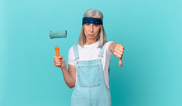 Kobieta w średnim wieku z siwymi włosami czuje krzyż, pokazując kciuk w dół wałkiem malującym ścianę