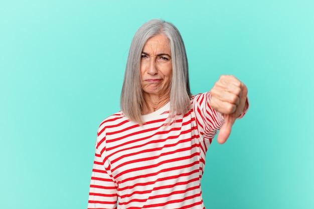 Kobieta w średnim wieku z siwymi włosami czuje krzyż, pokazując kciuk w dół