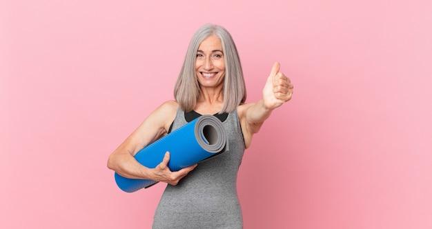 Kobieta w średnim wieku z siwymi włosami czuje się dumna, uśmiecha się pozytywnie z kciukami do góry i trzyma matę do jogi