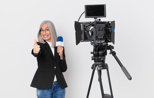 Kobieta w średnim wieku z siwymi włosami czuje się dumna, uśmiecha się pozytywnie z kciukami do góry i trzyma mikrofon. koncepcja prezentera telewizyjnego