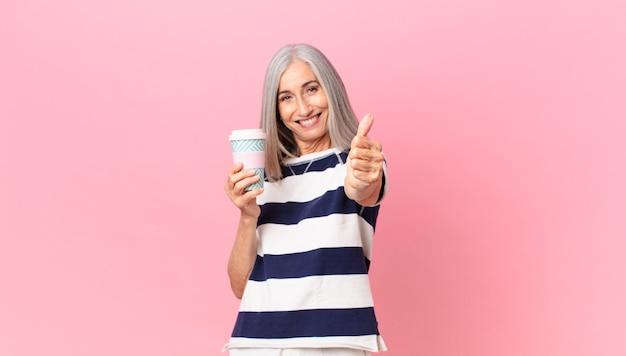 Kobieta w średnim wieku z siwymi włosami czuje się dumna, uśmiecha się pozytywnie z kciukami do góry i trzyma pojemnik na kawę na wynos