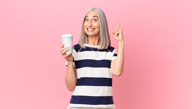 Kobieta w średnim wieku z siwymi włosami czuje się jak szczęśliwy i podekscytowany geniusz po zrealizowaniu pomysłu i trzymaniu pojemnika na kawę na wynos