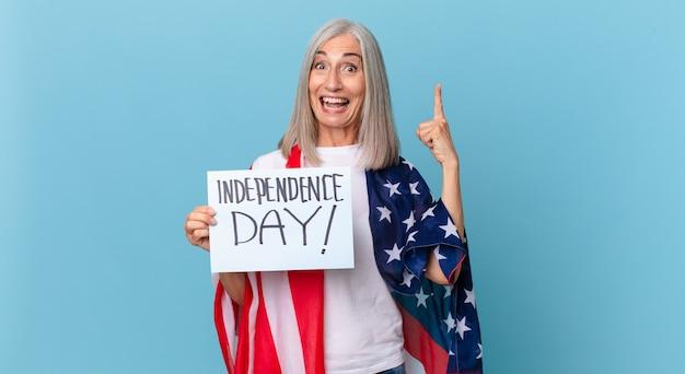 Kobieta w średnim wieku z siwymi włosami czuje się jak szczęśliwy i podekscytowany geniusz po zrealizowaniu pomysłu. koncepcja dnia niepodległości