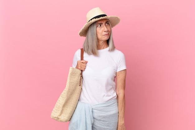 Kobieta w średnim wieku z siwymi włosami czuje się smutna, zdenerwowana lub zła i patrzy w bok. koncepcja lato