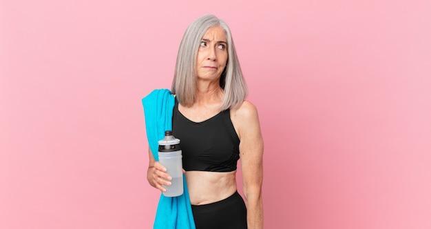 Kobieta w średnim wieku z siwymi włosami czuje się smutna, zdenerwowana lub zła i patrzy w bok z ręcznikiem i bidonem. koncepcja fitness