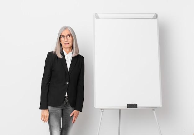 Kobieta w średnim wieku z siwymi włosami czuje się smutna, zdenerwowana lub zła i patrzy z boku na miejsce na kopię. pomysł na biznes
