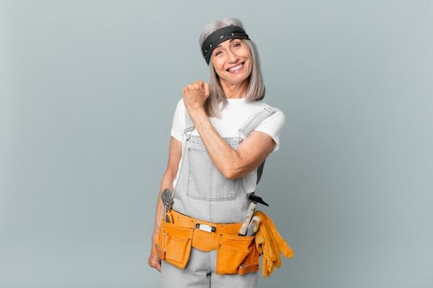 Kobieta w średnim wieku z siwymi włosami czuje się szczęśliwa i staje przed wyzwaniem lub świętuje i nosi odzież roboczą i narzędzia. koncepcja sprzątania