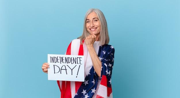 Kobieta w średnim wieku z siwymi włosami czuje się szczęśliwa i staje przed wyzwaniem lub świętuje. koncepcja dnia niepodległości