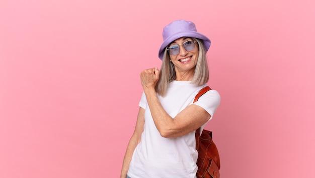 Kobieta w średnim wieku z siwymi włosami czuje się szczęśliwa i staje przed wyzwaniem lub świętuje. koncepcja lato