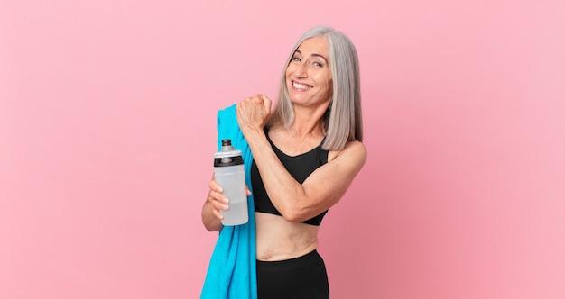 Kobieta w średnim wieku z siwymi włosami czuje się szczęśliwa i staje przed wyzwaniem lub świętuje z ręcznikiem i bidonem. koncepcja fitness
