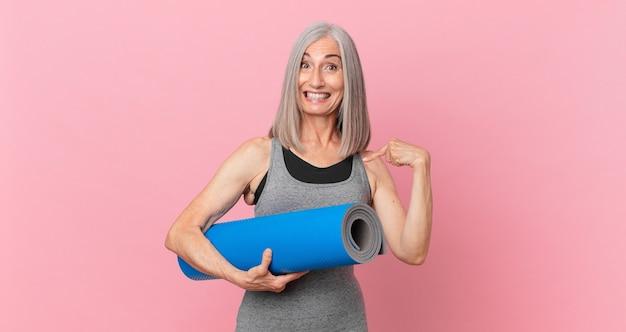 Kobieta w średnim wieku z siwymi włosami czuje się szczęśliwa i wskazuje na siebie z podekscytowaną i trzymającą matę do jogi. koncepcja fitness