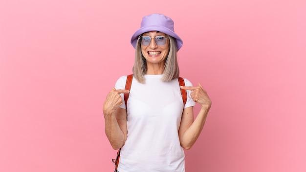 Kobieta w średnim wieku z siwymi włosami czuje się szczęśliwa i wskazuje na siebie z podekscytowaniem. koncepcja lato