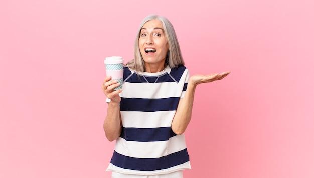 Kobieta w średnim wieku z siwymi włosami czuje się szczęśliwa i zdumiona czymś niewiarygodnym i trzyma pojemnik na kawę na wynos