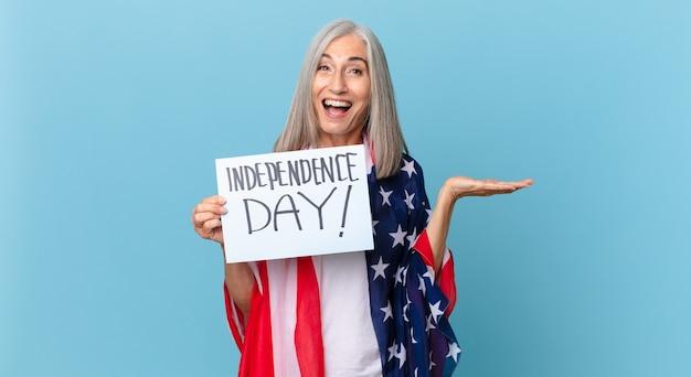 Kobieta W średnim Wieku Z Siwymi Włosami Czuje Się Szczęśliwa I Zdumiona Czymś Niewiarygodnym. Koncepcja Dnia Niepodległości Premium Zdjęcia