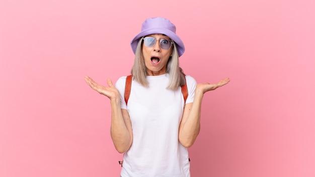 Kobieta w średnim wieku z siwymi włosami czuje się szczęśliwa i zdumiona czymś niewiarygodnym. koncepcja lato