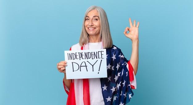 Kobieta w średnim wieku z siwymi włosami czuje się szczęśliwa, okazując aprobatę dobrym gestem. koncepcja dnia niepodległości
