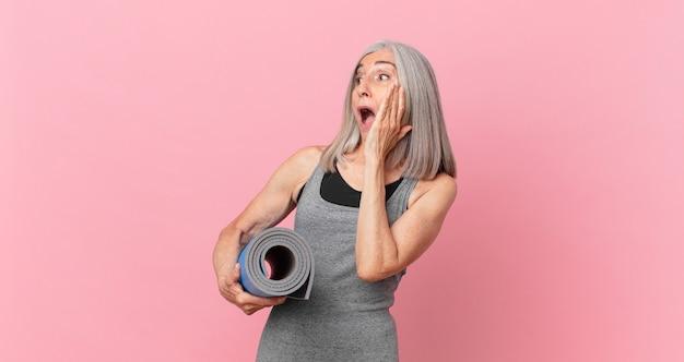 Kobieta w średnim wieku z siwymi włosami czuje się szczęśliwa, podekscytowana i zaskoczona i trzyma matę do jogi. koncepcja fitness