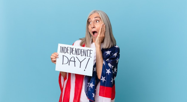 Kobieta W średnim Wieku Z Siwymi Włosami Czuje Się Szczęśliwa, Podekscytowana I Zaskoczona. Koncepcja Dnia Niepodległości Premium Zdjęcia