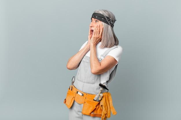 Kobieta w średnim wieku z siwymi włosami czuje się szczęśliwa, podekscytowana i zaskoczona oraz nosi odzież roboczą i narzędzia. koncepcja sprzątania