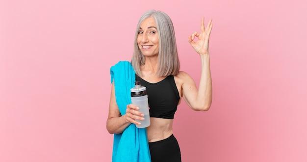 Kobieta w średnim wieku z siwymi włosami czuje się szczęśliwa, pokazując aprobatę dobrym gestem ręcznikiem i bidonem. koncepcja fitness