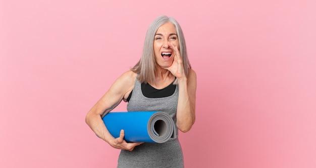 Kobieta w średnim wieku z siwymi włosami czuje się szczęśliwa, wydając wielki okrzyk z rękami przy ustach i trzymając matę do jogi. koncepcja fitness
