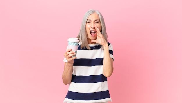 Kobieta w średnim wieku z siwymi włosami czuje się szczęśliwa, wydając wielki okrzyk z rękami przy ustach i trzymając pojemnik na kawę na wynos