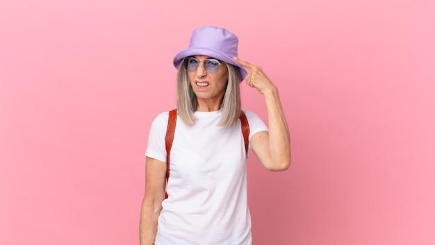 Kobieta w średnim wieku z siwymi włosami czuje się zdezorientowana i zakłopotana, pokazując, że jesteś szalony. koncepcja lato