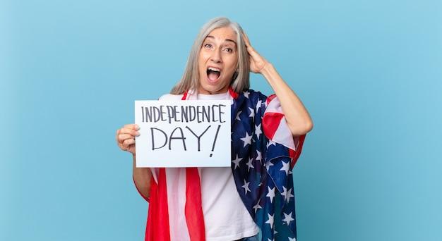 Kobieta W średnim Wieku Z Siwymi Włosami Czuje Się Zestresowana, Niespokojna Lub Przestraszona, Z Rękami Na Głowie. Koncepcja Dnia Niepodległości Premium Zdjęcia