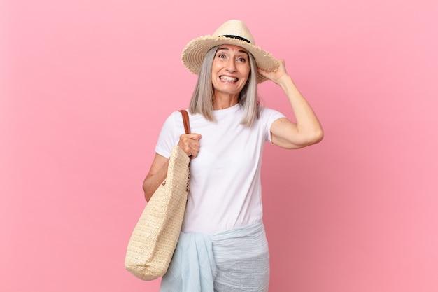 Kobieta w średnim wieku z siwymi włosami czuje się zestresowana, niespokojna lub przestraszona, z rękami na głowie. koncepcja lato