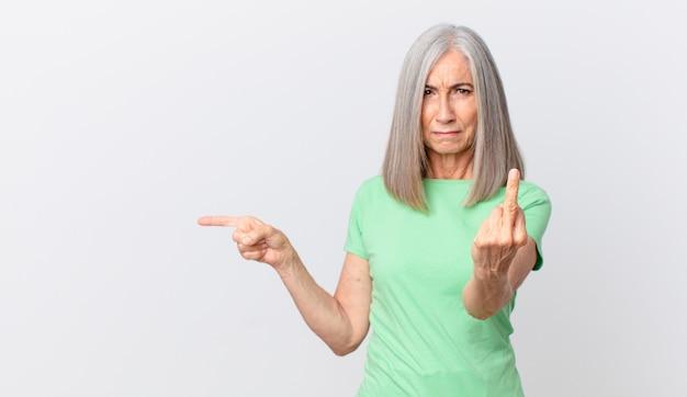 Kobieta w średnim wieku z siwymi włosami czuje się zła, zirytowana, buntownicza i agresywna i wskazuje na bok
