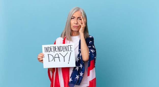 Kobieta w średnim wieku z siwymi włosami czuje się znudzona, sfrustrowana i senna po męczącym dniu. koncepcja dnia niepodległości