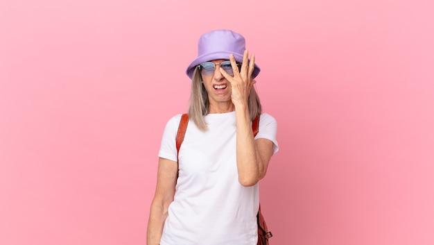Kobieta w średnim wieku z siwymi włosami czuje się znudzona, sfrustrowana i senna po męczącym dniu. koncepcja lato