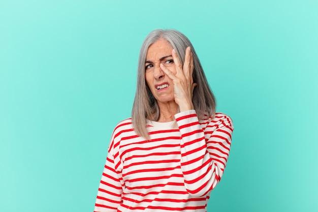 Kobieta w średnim wieku z siwymi włosami czuje się znudzona, sfrustrowana i senna po męczącym dniu