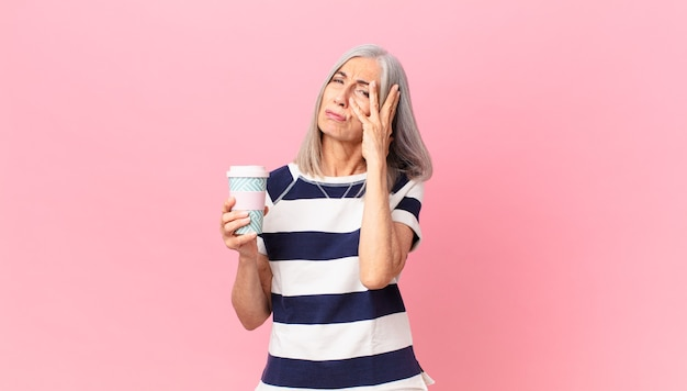 Kobieta w średnim wieku z siwymi włosami czuje się znudzona, sfrustrowana i senna po męczącym i trzymającym pojemnik na kawę na wynos