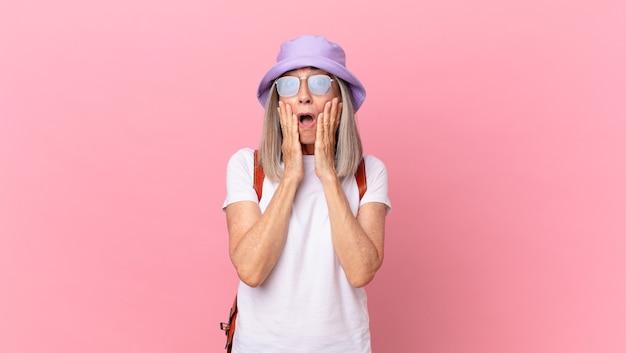 Kobieta w średnim wieku z siwymi włosami czuje się zszokowana i przestraszona. koncepcja lato