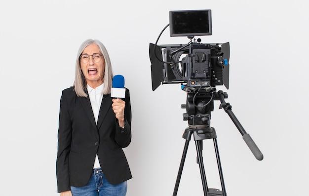 Kobieta w średnim wieku z siwymi włosami, krzycząca agresywnie, wyglądająca na bardzo rozgniewaną i trzymająca mikrofon. koncepcja prezentera telewizyjnego