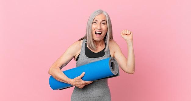 Kobieta w średnim wieku z siwymi włosami, krzycząca agresywnie z gniewnym wyrazem twarzy i trzymająca matę do jogi. koncepcja fitness