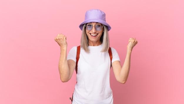 Kobieta w średnim wieku z siwymi włosami, krzycząca agresywnie z gniewnym wyrazem twarzy. koncepcja lato