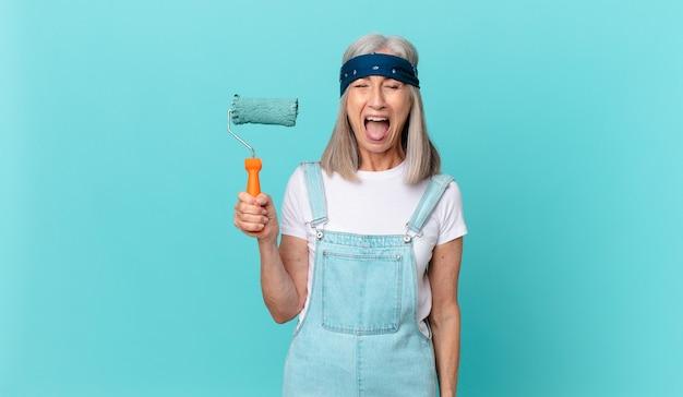 Kobieta w średnim wieku z siwymi włosami krzyczy agresywnie, wygląda na bardzo złą, gdy wałkiem maluje ścianę