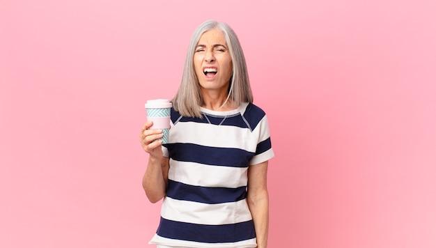 Kobieta w średnim wieku z siwymi włosami krzyczy agresywnie, wygląda na bardzo złą i trzyma pojemnik na kawę na wynos