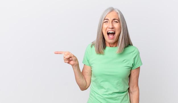 Kobieta w średnim wieku z siwymi włosami krzyczy agresywnie, wygląda na bardzo złą i wskazuje na bok