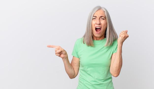 Kobieta w średnim wieku z siwymi włosami krzyczy agresywnie z gniewnym wyrazem twarzy i wskazuje na bok