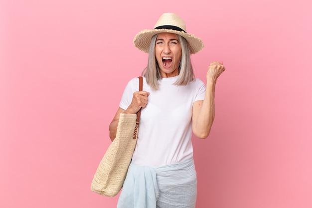 Kobieta w średnim wieku z siwymi włosami krzyczy agresywnie z gniewnym wyrazem twarzy. koncepcja lato
