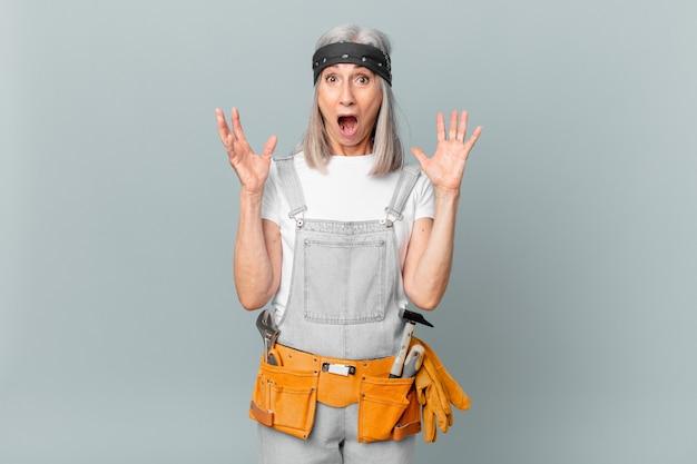 Kobieta w średnim wieku z siwymi włosami krzyczy z rękami w górze i ma na sobie odzież roboczą i narzędzia. koncepcja sprzątania
