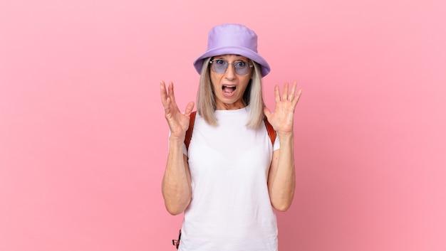 Kobieta w średnim wieku z siwymi włosami krzyczy z rękami w górze. koncepcja lato