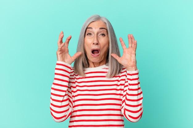 Kobieta w średnim wieku z siwymi włosami krzyczy z rękami w górze
